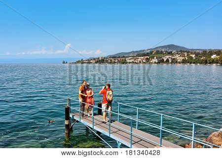Man Taking Photos Of Couple On Geneva Lake In Montreux