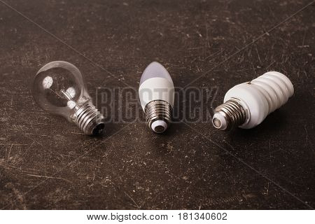 Electric LED bulb incandescent lamp fluorescent lamp on a dark marble background. To save energy. Eco concept. Electric lamp