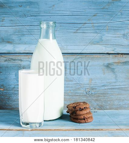 Chocolate oat meal cookies with milk on rustic wooden table.