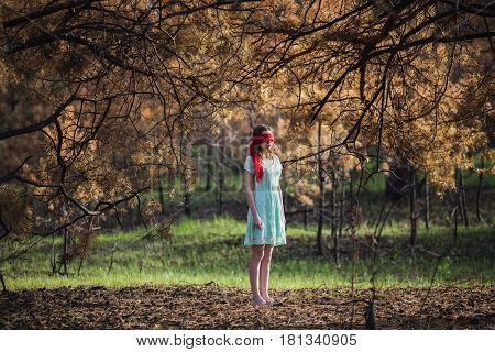 Lost in forest. Slavery. Very cute young girl with a blindfold red ribbon in forest. Doll appearance. Woman with brown hair in a turquoise dress on nature in forest. Long hair. Natural light. Model posing on the nature in forest. Kidnapping