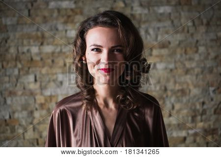 Girl Pin Up smile with brunette hair and retro make-up with red lips in a bathrobe on a dark background. Girl with smile sitting on the bed . Vintage image. Smile on face