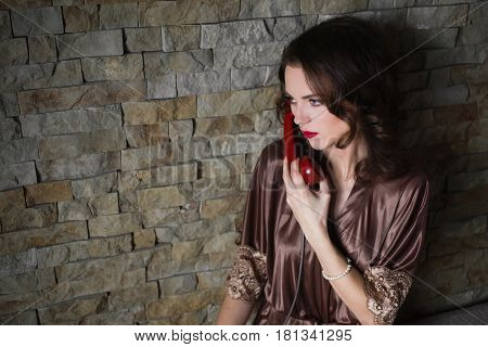 Girl Pinup with brunette hair and retro make-up with red lips in a bathrobe on a dark background talking phone. Girl sitting on the bed. Vintage image. Woman talking on the phone. Disk phone
