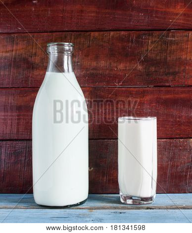 Bottle and glass of milk close-up on wooden background.