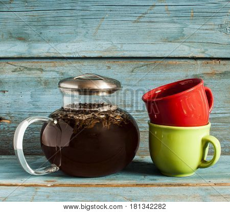 transparent glass teapot with black tea and colorful teacups on wooden table