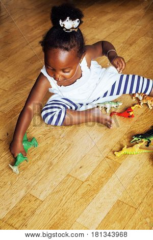 little cute african american girl playing with animal toys at home, pretty adorable princess in interior happy smiling, lifestyle people concept close up