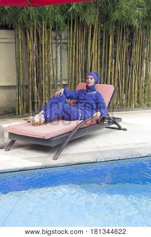 attractive woman in a Muslim swimwear burkini on a beach plank bed near the pool