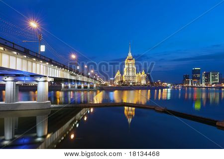 Night Moscow. Moscow River. A kind from Krasnopresnenskaya quay on hotel Ukraine and on the New Arbat bridge. poster