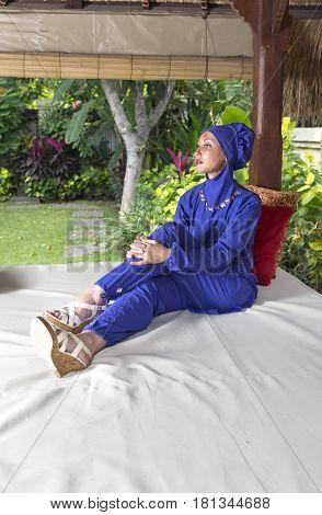 attractive woman in a Muslim swimwear burkini in gazebo for rest in a garden