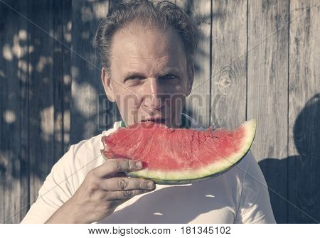 the happy man with a piece of a water-melon with a vintage effect