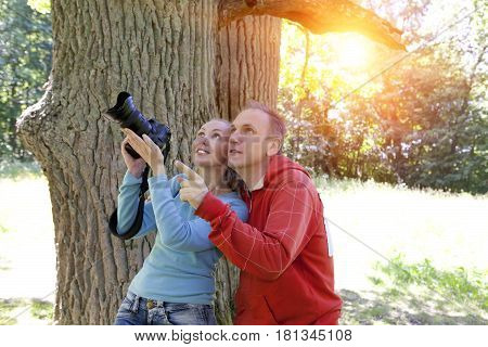 man and woman near an oak in summer day show to the side and photograph on the big camera