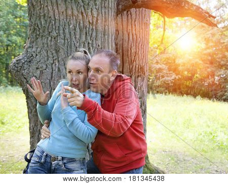 man and woman near an oak in summer day something was seen aside and looked scared and with astonishment