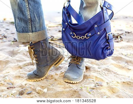 Female legs in blue jeans and boots with a blue bag on a background of the sandy beach