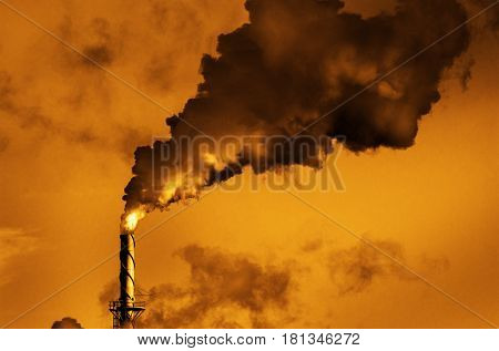 Factory smokestack chimney piping smoke or steam into the air pollution