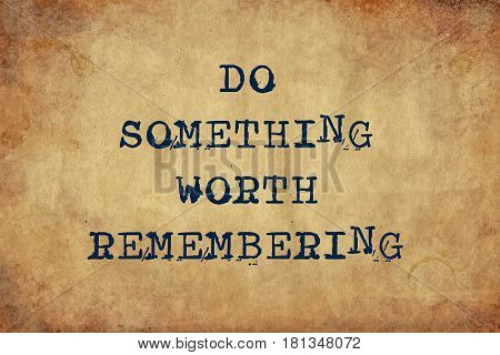 Inspiring motivation quote of do something worth remembering with typewriter text. Distressed Old Paper with Typing image.
