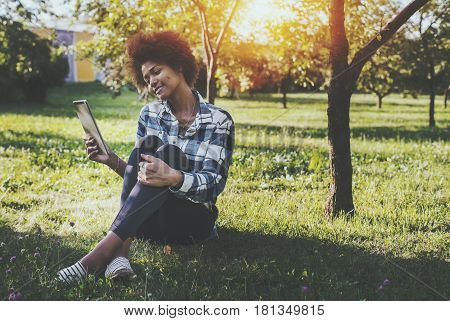 Charming young biracial girl with curly afro hair and touch pad sitting on spring meadow near apple tree and talking with her boyfriend via video call with copy space for your text advertising message