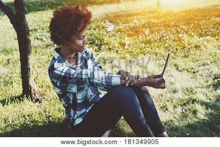 Charming black female teen with digital tablet sitting in park on summertime and reading eBook attractive mixed girl with curly afro hair and touch pad sitting on grass of meadow on spring sunny day