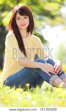 Young woman in the park with flowers. Beauty nature scene with colorful background, trees and flowers at spring season. Outdoor lifestyle. Happy smiling woman relax on green grass