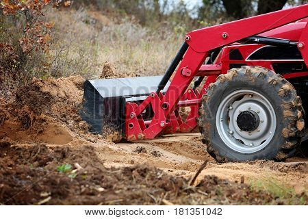 Tractor front end loader with dirt on construction side