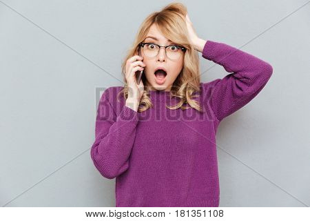 Surprised woman wearing violet sweater talking on phone and touching her hair isolated