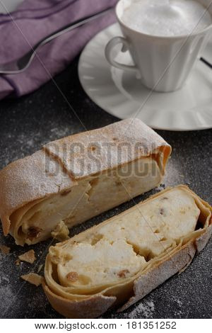 Strudel with cottage cheese and raisins under powdered sugar and a cup of coffee late