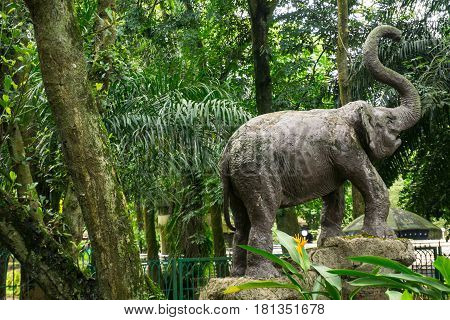 elephant statue made from concrete standing in the middle of green garden photo taken in Ragunan zoo Jakarta Indonesia java