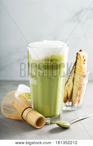 Matcha latte with milk foam in tall glass with biscotti on light background