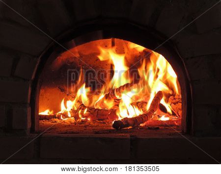 The firewood burning in a rustic stove