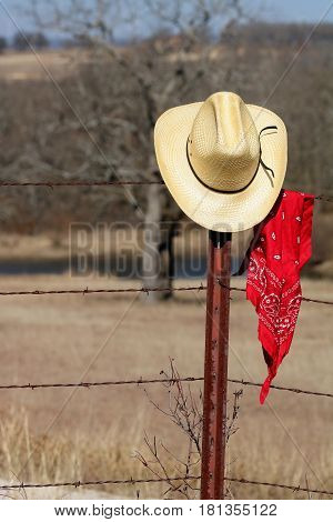 A yellow straw cowboy hat hanging on a barbed wire fence post with a red bandana hanging beside it. Trees and field in the background.