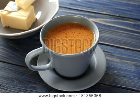 Cup of tasty butter coffee on wooden table