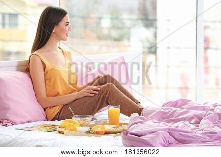 Beautiful young woman going to have breakfast while sitting on bed at home