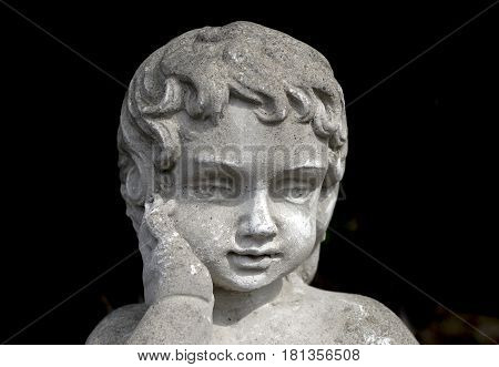 Vintage stone garden statue of young girl with hand on cheek thoughtful beautiful expression dark background