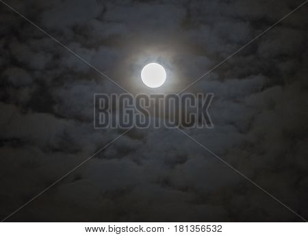 Soft shining full moon surrounded by moody fantasy-like clouds night sky scene
