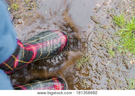 Closeup of person jumping in rain puddle with rubber boots on spring fun and outdoor activities concept