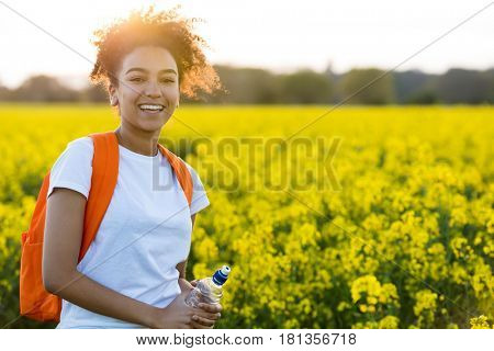 Outdoor portrait of beautiful happy mixed race African American girl teenager female young woman with water bottle hiking with back pack in a field of yellow flowers at sunset golden evening sunshine