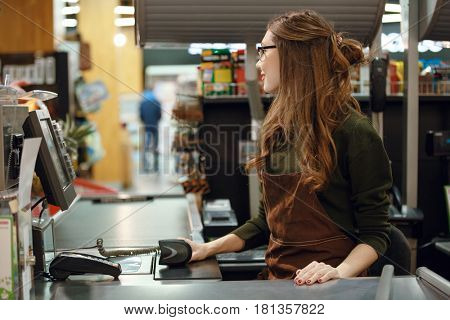 Picture of cashier woman on workspace in supermarket shop. Looking aside.