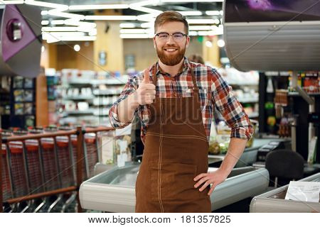 Picture of happy cashier man on workspace in supermarket shop. Looking at camera showing thumbs up.