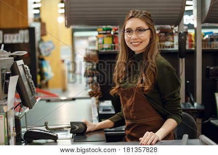 Image of happy cashier woman on workspace in supermarket shop. Looking aside.