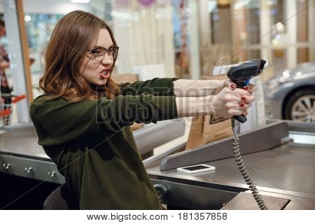 Picture of cashier lady on workspace in supermarket shop have fun. Looking aside.
