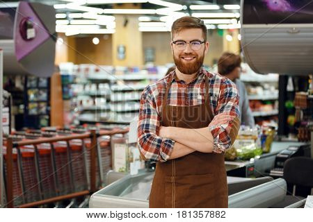 Picture of cashier man on workspace in supermarket shop. Looking at camera.