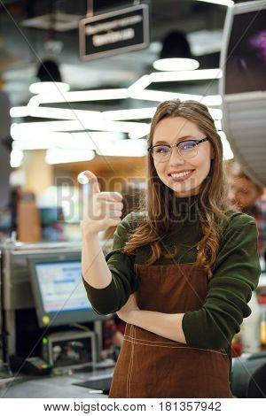 Photo of happy cashier woman on workspace in supermarket shop. Looking at camera showing thumbs up.