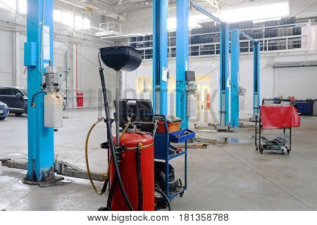 Interior of a car repair station. There is a device for oil changing on the frontground