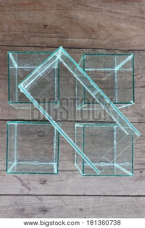 Square glass bowl for fish bowls placed on a wooden background.