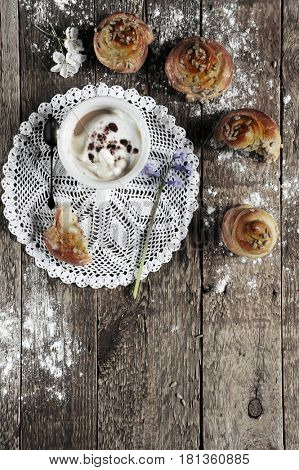 Four baked wriggled buns with coffee on dark rustic wooden background.