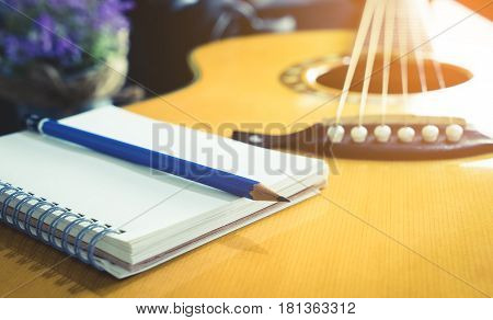 Guitarist Songwriter with blank notebook and pencil for song music writing