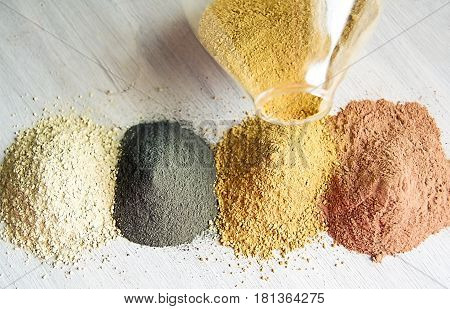 Yellow red white and black cosmetic cleansing clay for face and body. Healing Clay is a natural product. Dry cosmetic clay on a wooden background. Selective focus
