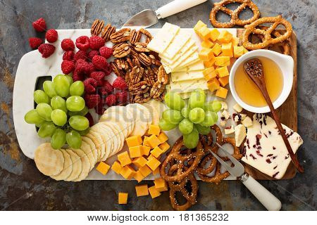 Cheese and snacks platter with honey and fresh fruit top view