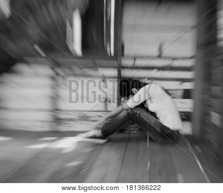 Woman sitting strain ,unhappy In the corner on the bow the knee,White and black,blur