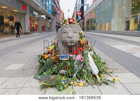 STOCKHOLM SWEDEN - APR 12 2017: Lots of flowers on concrete lion on Drottninggatan in central Stockholm from people paying respect to the victims in the terror attack in Stockholm April 07 2017. April 13 2017 in Stockholm Sweden