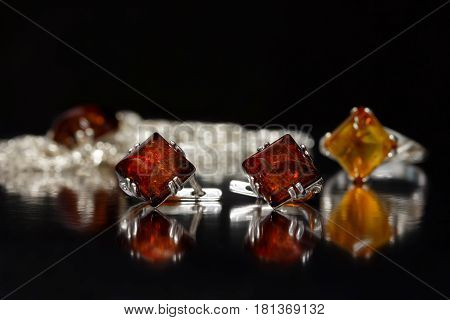 Closeup silver earrings rhombus with authentic natural baltic amber on black surface on background of ring and chain with pendant.