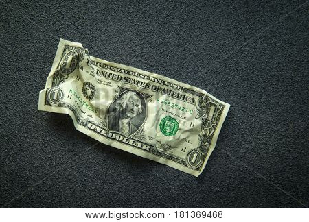 Crumpled one dollar bill on a gray background. Selective focus